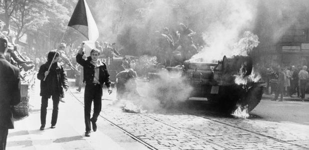 Tsjecho-Slowaken met hun vlag naast een brandende tank in Praag in 1968