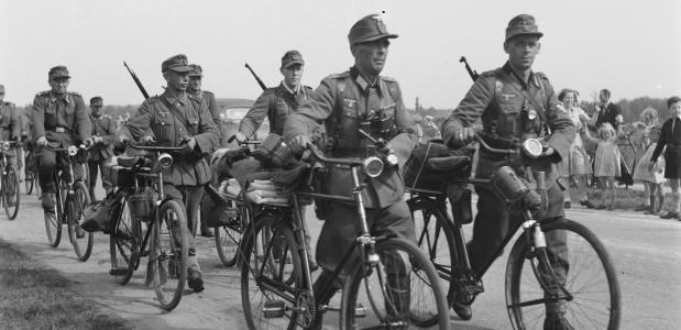 Militairen, lopend naast hun fietsen, gaan hun wapens en uitrusting inleveren na de Bevrijding