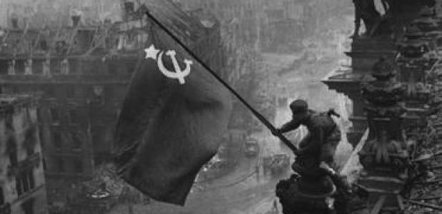 Een soldaat hijst de Sovjetvlag op de Berlijnse Reichstag, door Yevgeny Khaldei. Bron: Wikimedia Commons.
