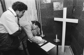 In een gebouw in de Bijlmermeer tekenen Surinamers een condoleanceregister.