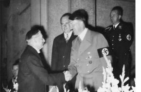 De Britse premier Chamberlain schudt glimlachend de hand van Adolf Hitler.