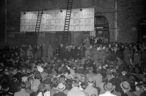 De uitslagen van de eerste naoorlogse verkiezingen worden groot getoond op de gevel van de Beurs van Berlage aan het Damrak.
